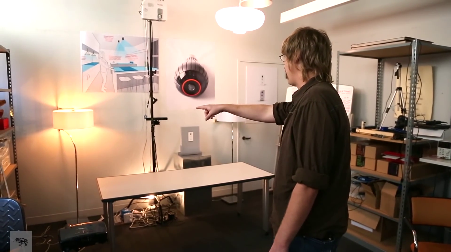 "Jared Ficklin demonstrates Room-E, a system combining voice and gestural interactions; a gesture (pointing at a lamp) is combined with voice input (""computer, turn off this light"") to turn off the correct lamp."
